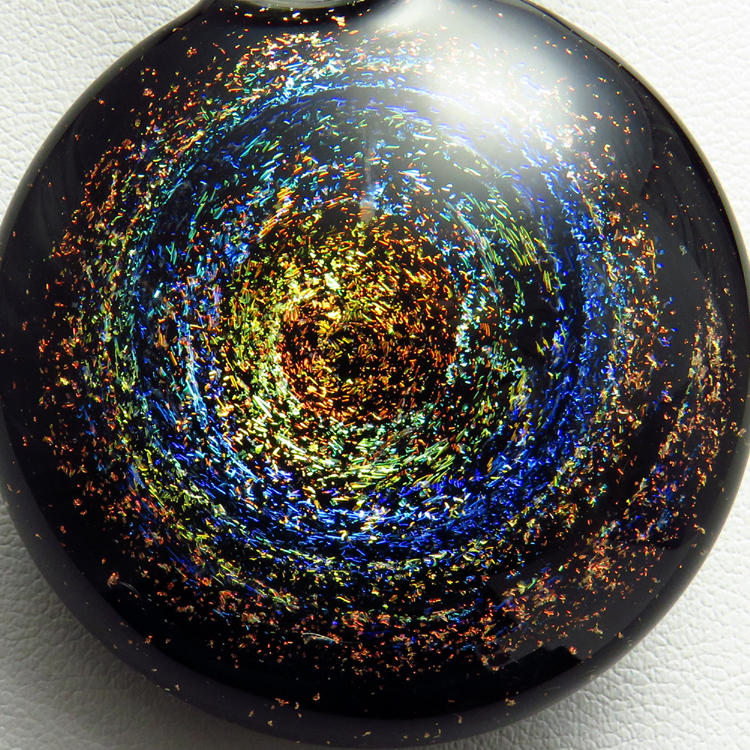Galaxy pendant necklace by Glenn Godden. Has real 3d depth inside and sparkles with colour shifting dichroic as it moves in the light